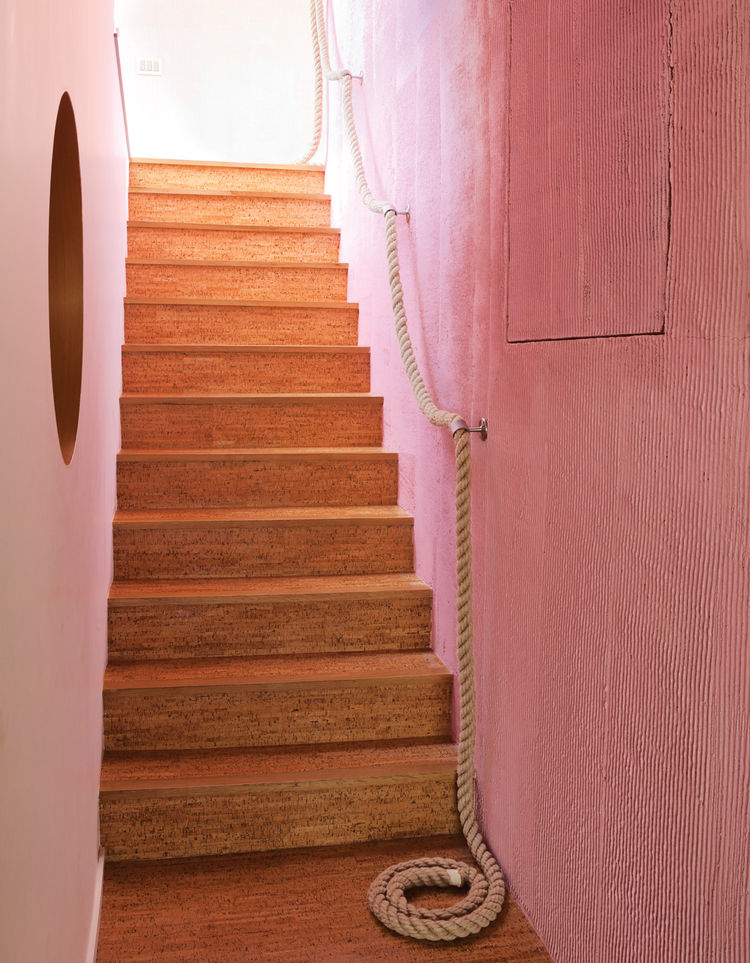 Modern cork stairs and rope railing by a pink wall