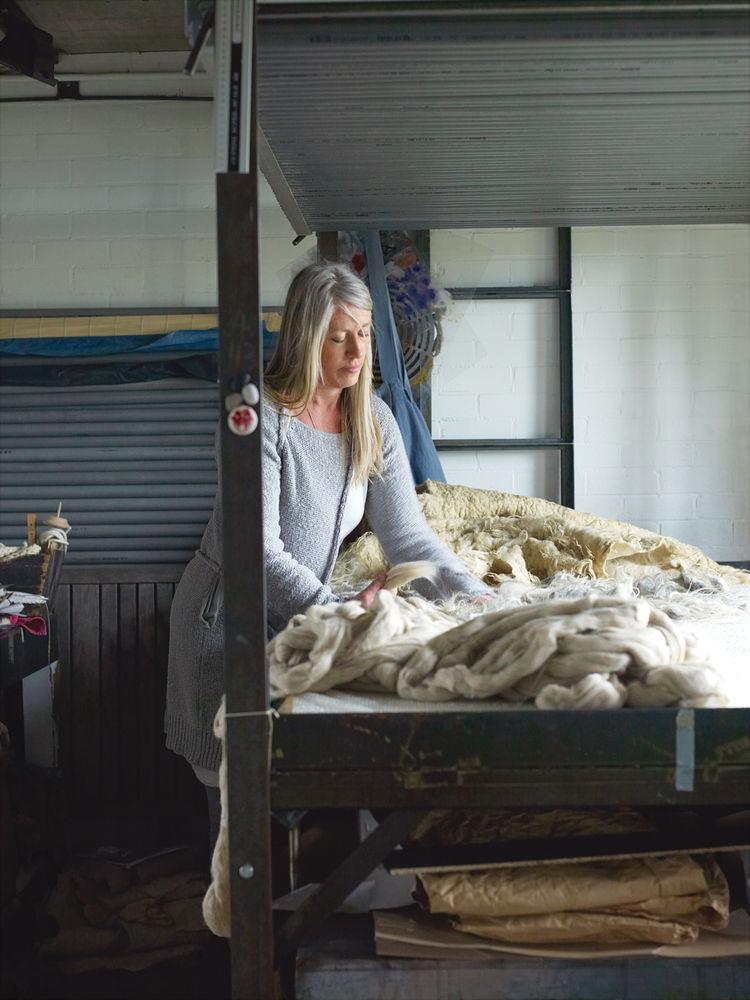 Feltmaker Paula Leen handling sheep wool