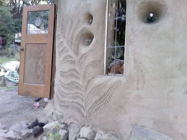 Fern design emblazoned exterior wall by Mud Girls