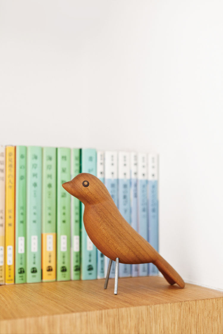 Bookshelf with wooden bird sculpture