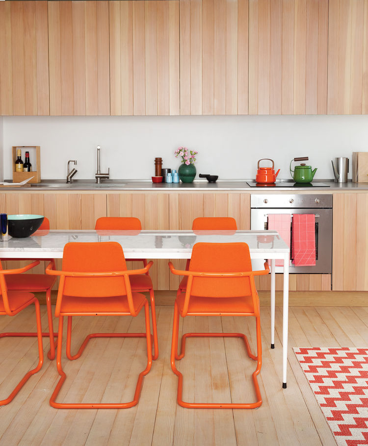 Modern custom-built kitchen with bright orange chairs
