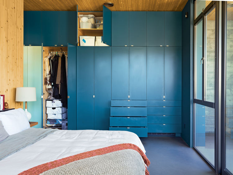 Modern master bedroom with blue closet cabinets