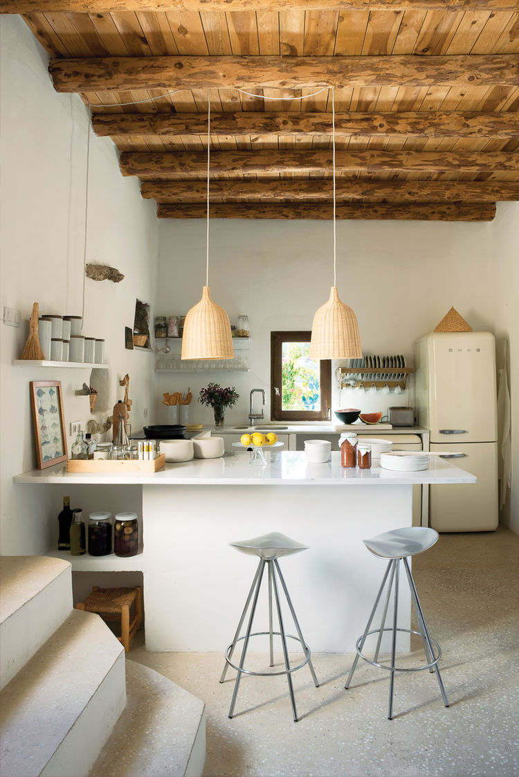 Modern kitchen with Pepe Cortès barstools and restored wooden beams