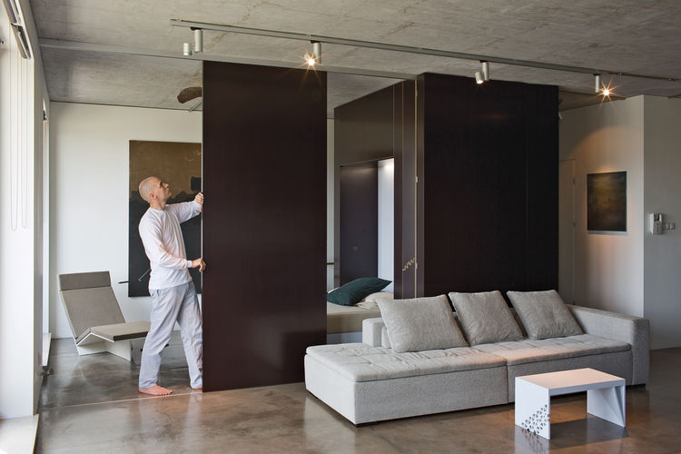 Modern living room with sliding plywood door and Mezzo sofa