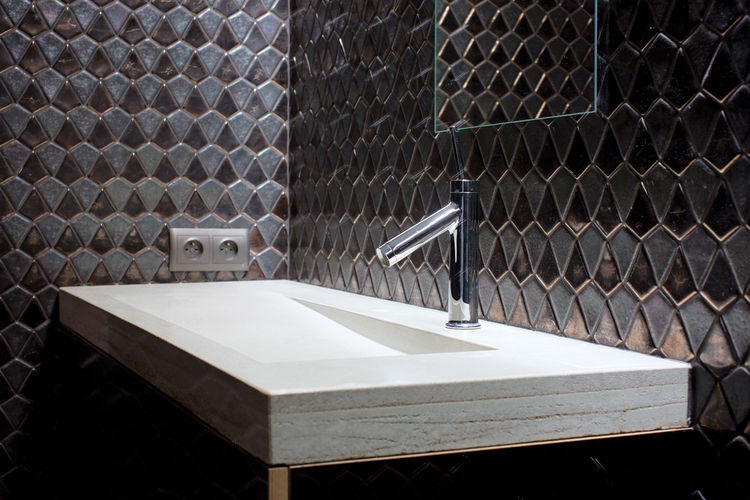 Modern bathroom sink area with black block tiled wall