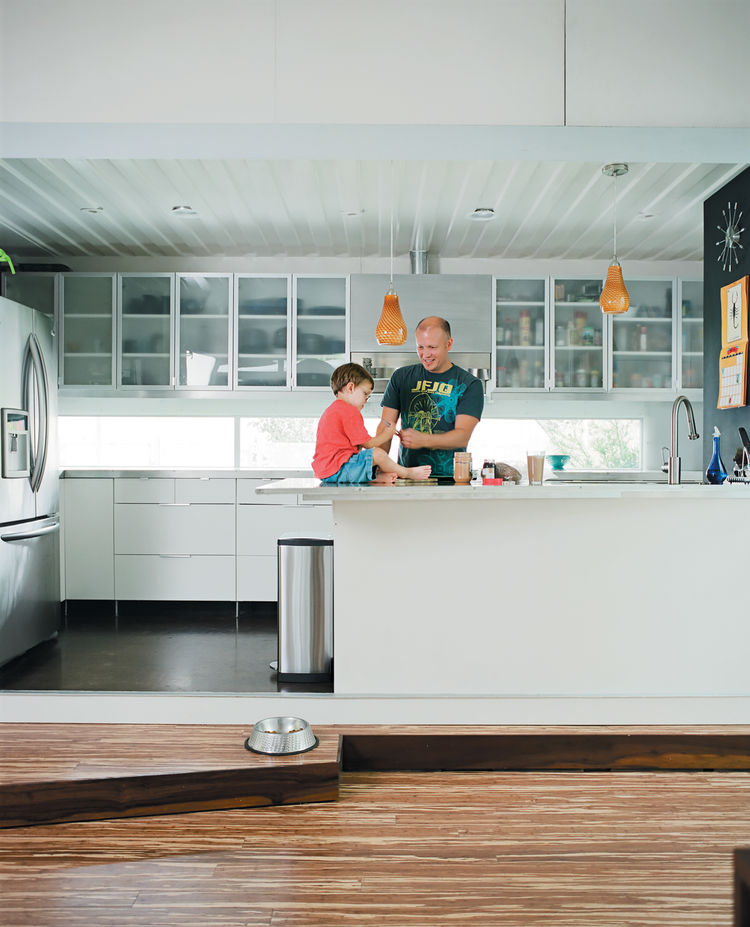In the kitchen, Freeman fixes a snack while Eli plays on the counter, one of his favorite spots in the house, second only to the kitchen steps. The horizontal window, which acts as a backsplash, is at the perfect height for looking outside when seated at