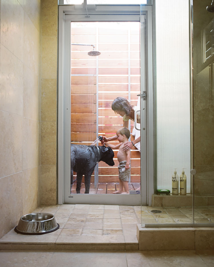 A door in the master bathroom connects the indoor shower to an outdoor one. Here, Feldmann and the couple's three-year-old son, Eli, wash their dog Arnold--named by the previous owner after the local St. Arnold Brewing Company.