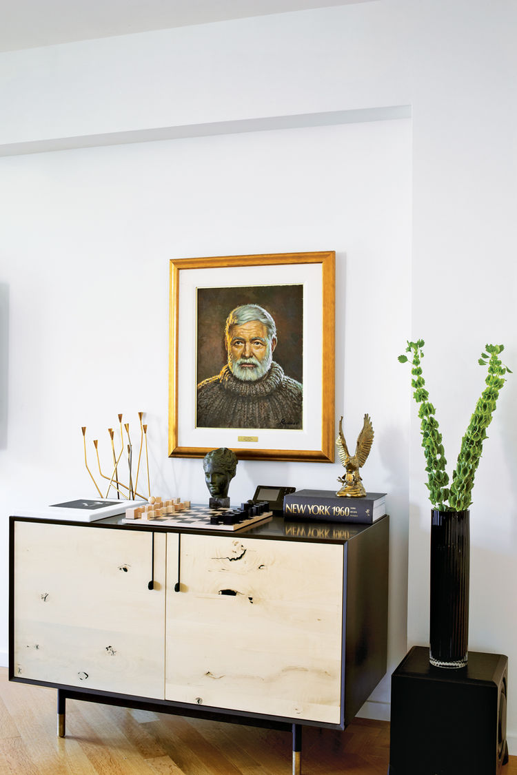 Modern living room corner with media console and Hemingway painting