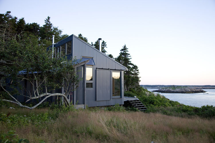 Waterfront cottage clad in aluminum panels