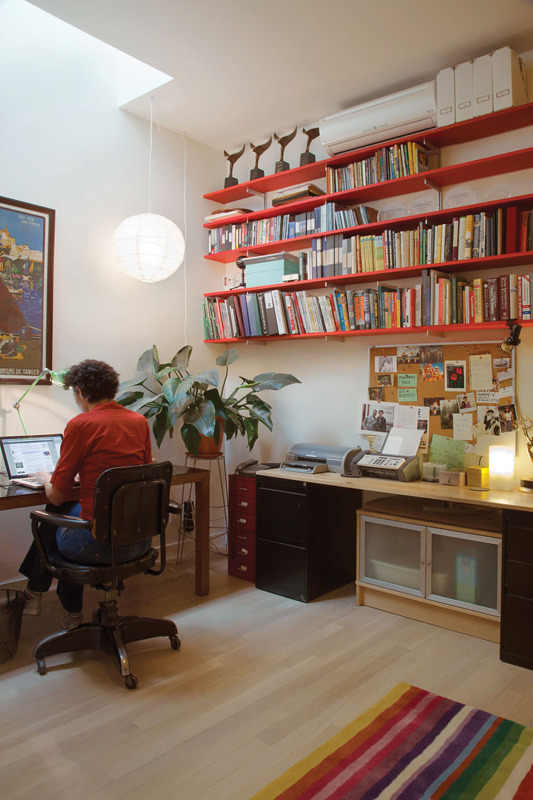 Office room with long red book shelves and pendant lamp