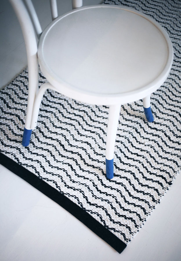 White-painted chair with blue-tipped legs and zig zag print rug