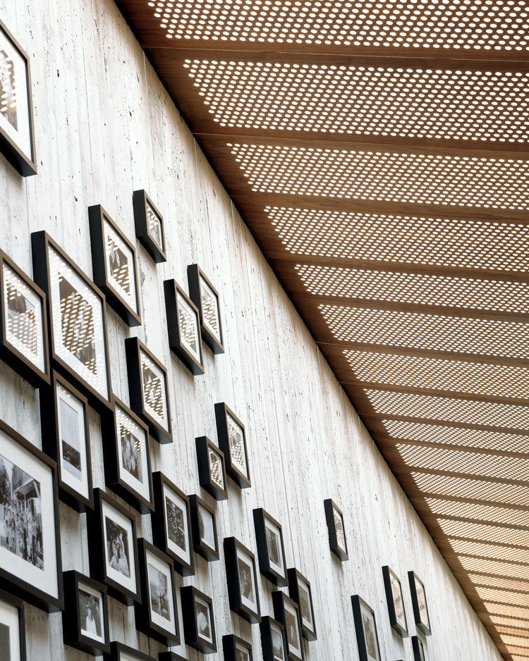 Clustered framed family photos hanging on the corridor wall