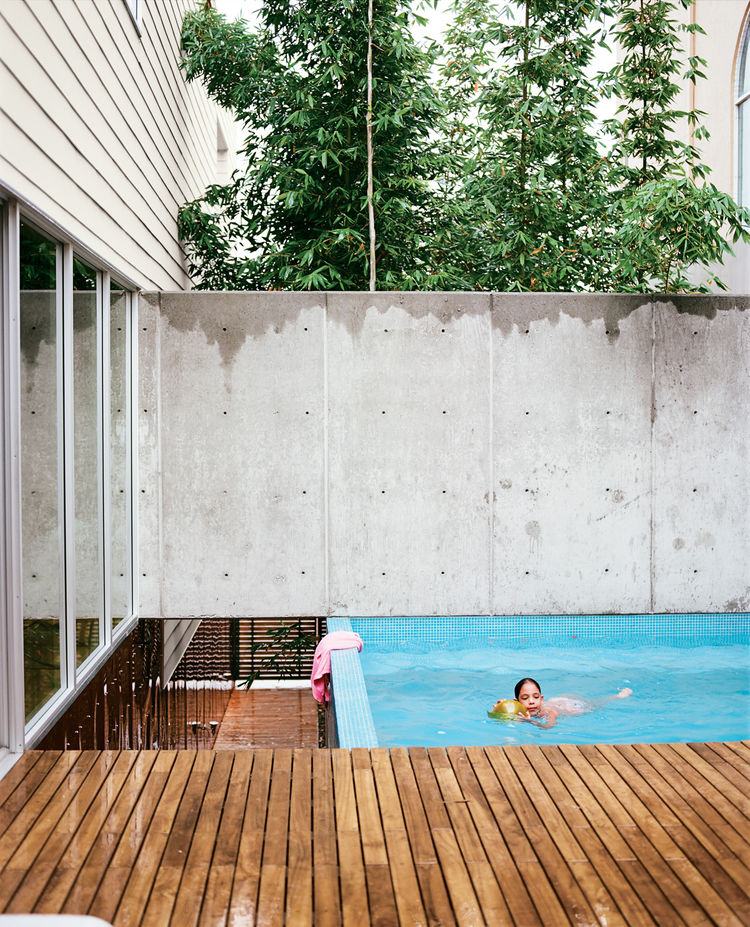 Outdoor swimming pool by tall concrete fence and wood plank walkway