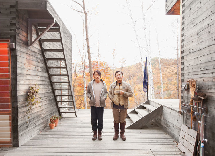 Setsumasa and Mami Kobayashi standing outside of their modern tent platform in Japan