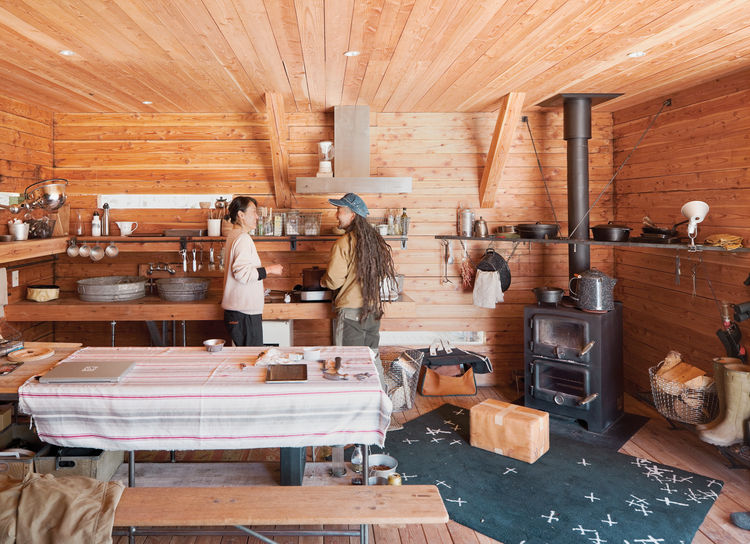 Mami Kobayashi and Ishii Hideaki in the kitchen with double-decker wood-burning stove
