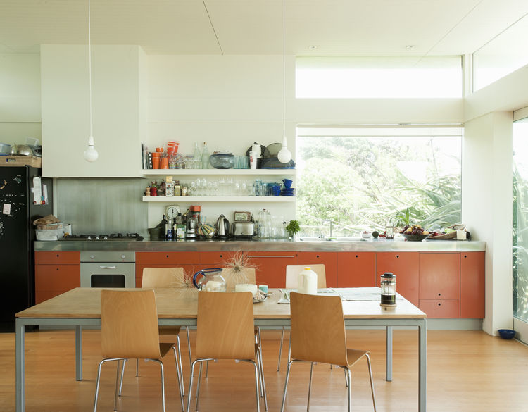 Kitchen area with orange-painted MDF cabinets