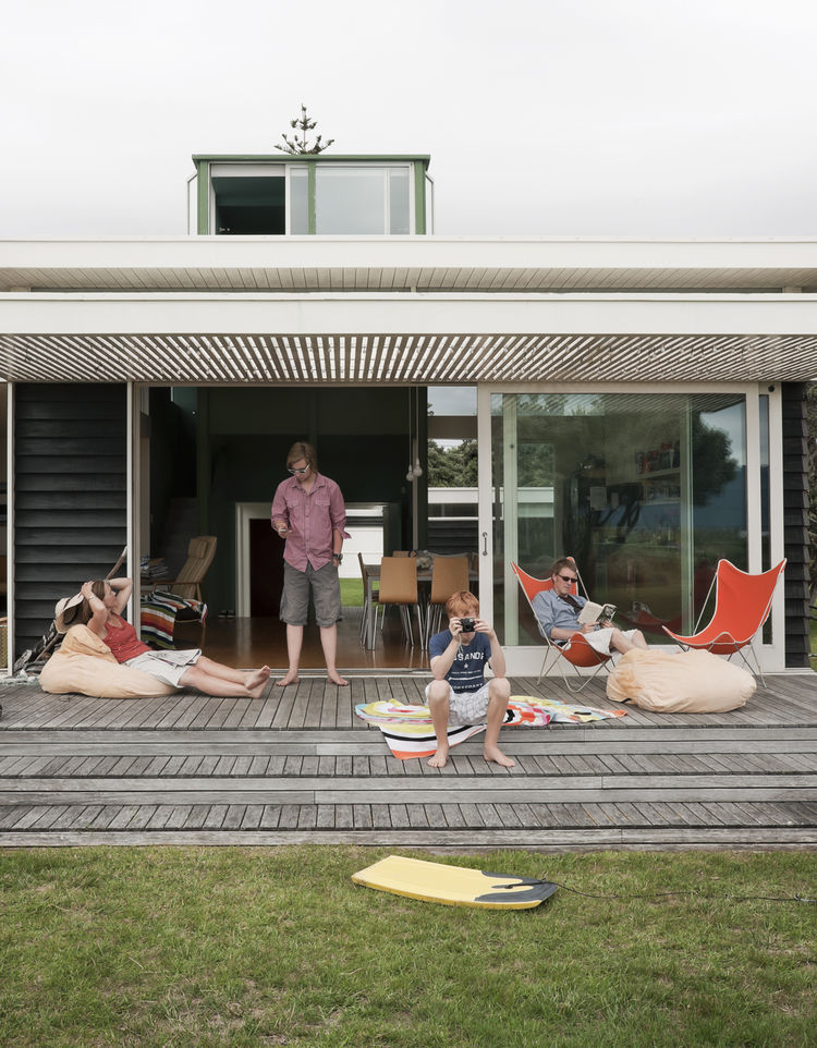Family in front of their beach house in New Zealand