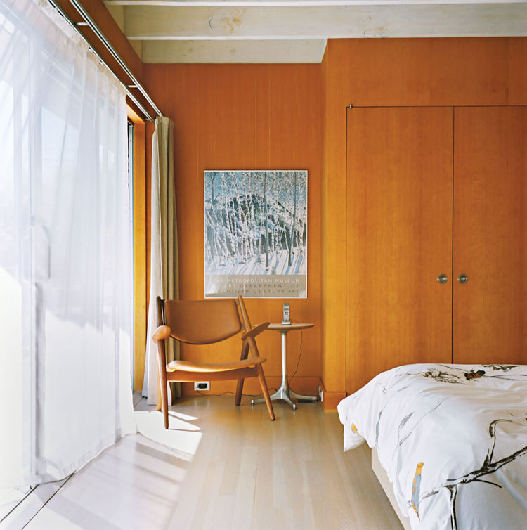 Master bedroom with sheer curtains and wood walls
