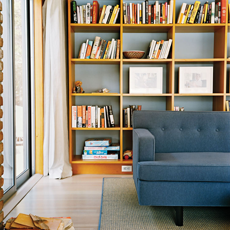 Living room with rectangular bookshelves and blue sofa