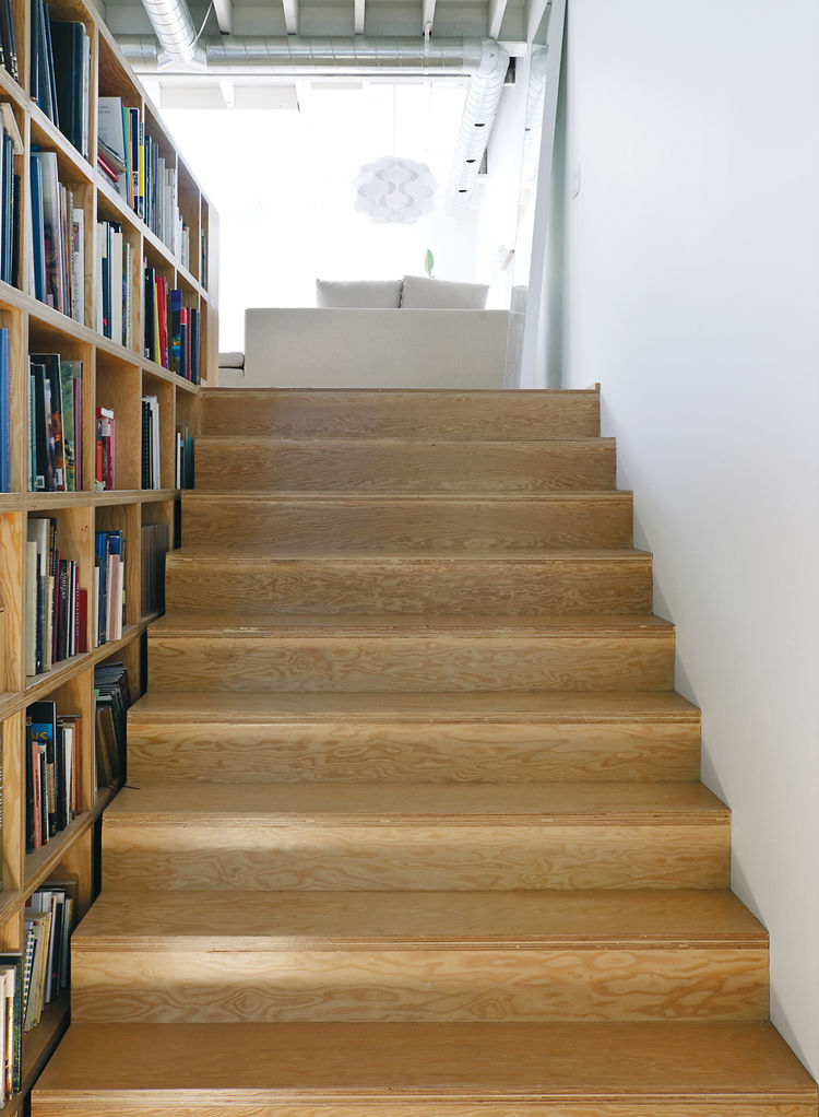 Natural grain wood stairs by bookshelves
