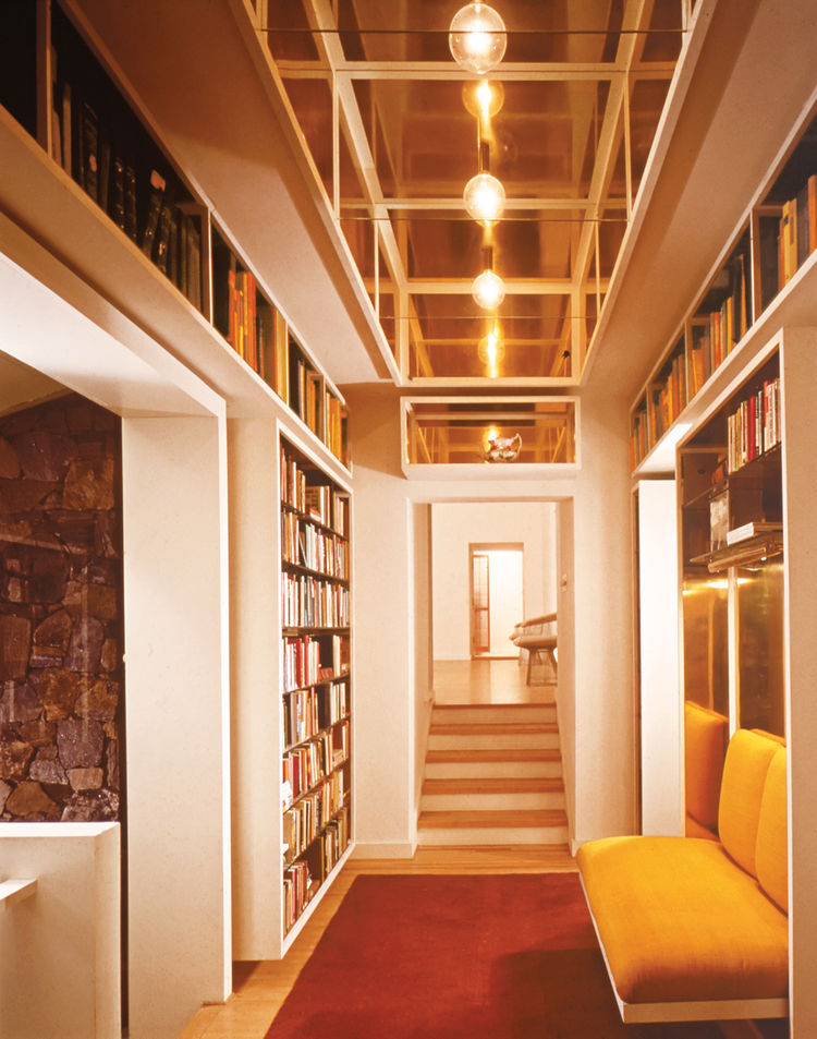 Hallway with built-in bookshelf and brass banquette