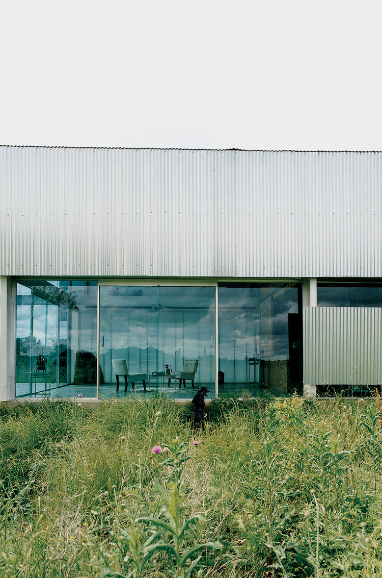 The front entrance of the Farley Studio in Cleburne, Texas, presents a clean, minimalist space—a stark contrast to the colorful clutter of the painting studio hidden behind corrugated-metal walls at the back of the house. Local context and cost of materia