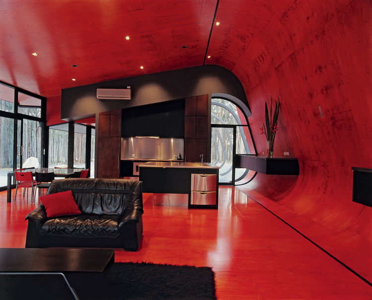 The glowing interior palette of bright pinks and reds is sharpened by jet-black steel frames, water tanks, and roofs, while black window frames and joinery bring out the red glow of the internal plywood lining.