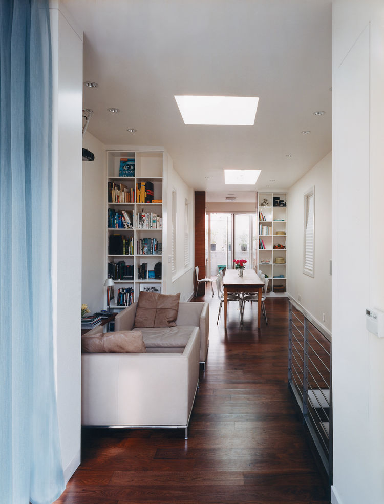 Once a split-level jumble of small, dark rooms, the main floor now offers a clear sight line from the patio straight through the kitchen, dining room, sitting area, and spare room to the street-facing window (with two skylights for added illumination).