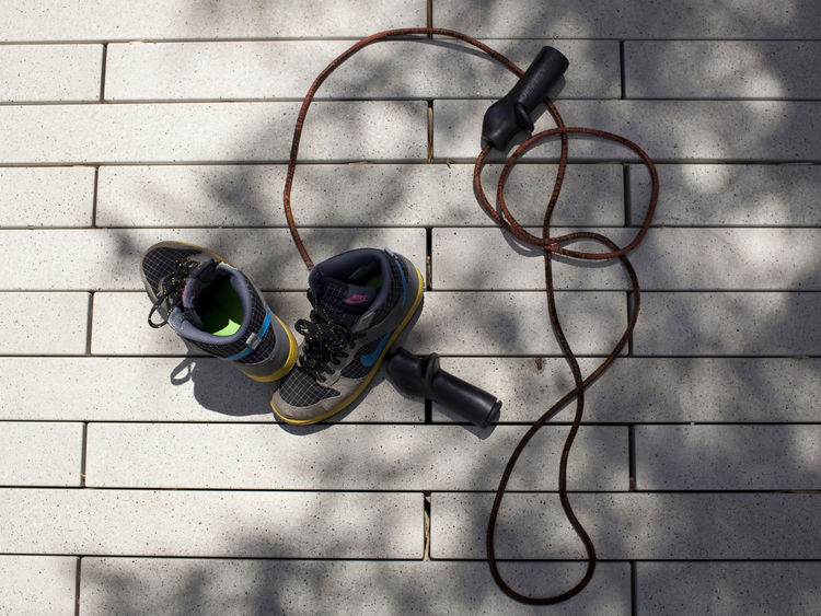 Childrens shoes and jump rope on the patio