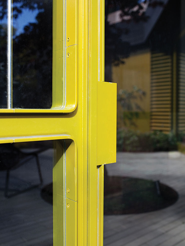 Yellow curving steel-and-glass window wall fabricated by Sand Studios