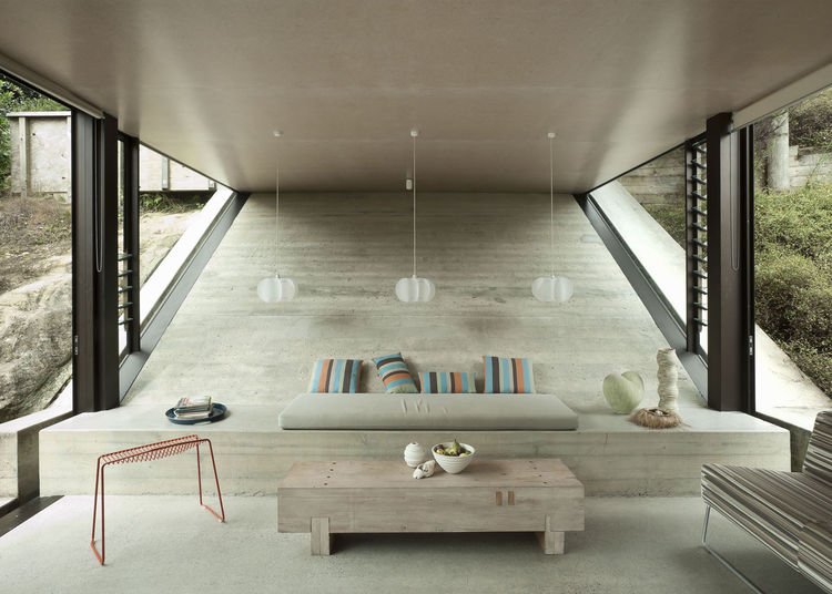 Living room area with sloping wall and concrete bench