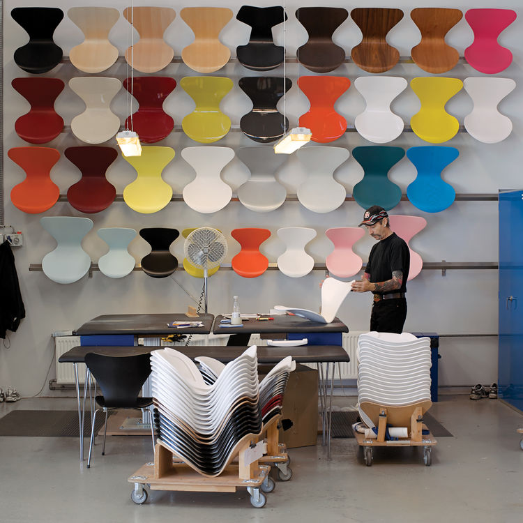 At the Fritz Hansen factory in Denmark, a worker inspects the paint finish of a Series 7 chair in front of a wall displaying just some of the wood and color options available.