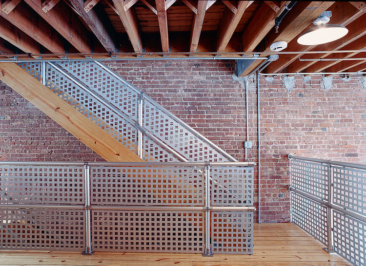 """Darcy Miro and her husband, Lars Weiss, built a four-story town house in Brooklyn. For the banisters and railings around their reading loft, they selected aluminum-magnesium Speed-Rail. They liked the """"inexpensive industrial"""" look it provided, explains Mi"""