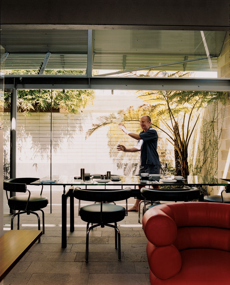 David Underwood, Langston-Jones's partner, opens the large glass doors that expand the interior of the small house out onto the sun-drenched courtyard garden. In keeping with Langston-Jones's love of Le Corbusier, the dining room chairs are LC7s and the t