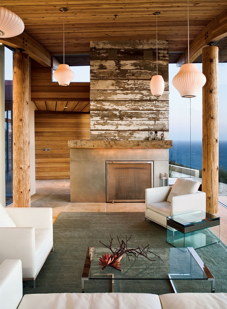 """For her home in Big Sur, California, Mary Ann Schicketanz of Carmel architecture firm Carver & Schicketanz conceived a reclaimed-wood fireplace for the living room. Additional warmth is garnered through the limestone flooring. <a href=""""http://www.dwell.co"""