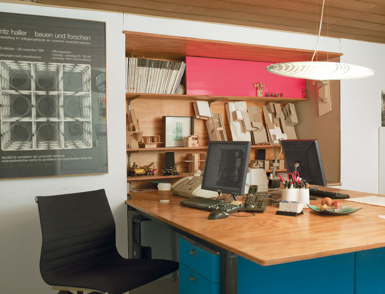 The architectural office below the living quarters is compact, with just enough space for shared workstations and a bookcase made of plywood and pink Plexiglas.