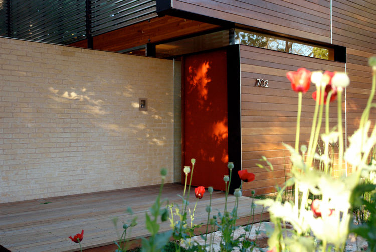 The bright red front door forms a complete piece with the glass panel beside it, such that the entire piece pivots when the entryway opens. Wolfe, a technology enthusiast, chose to substitute a standard lock and key system for a high-tech thumb-reader mec