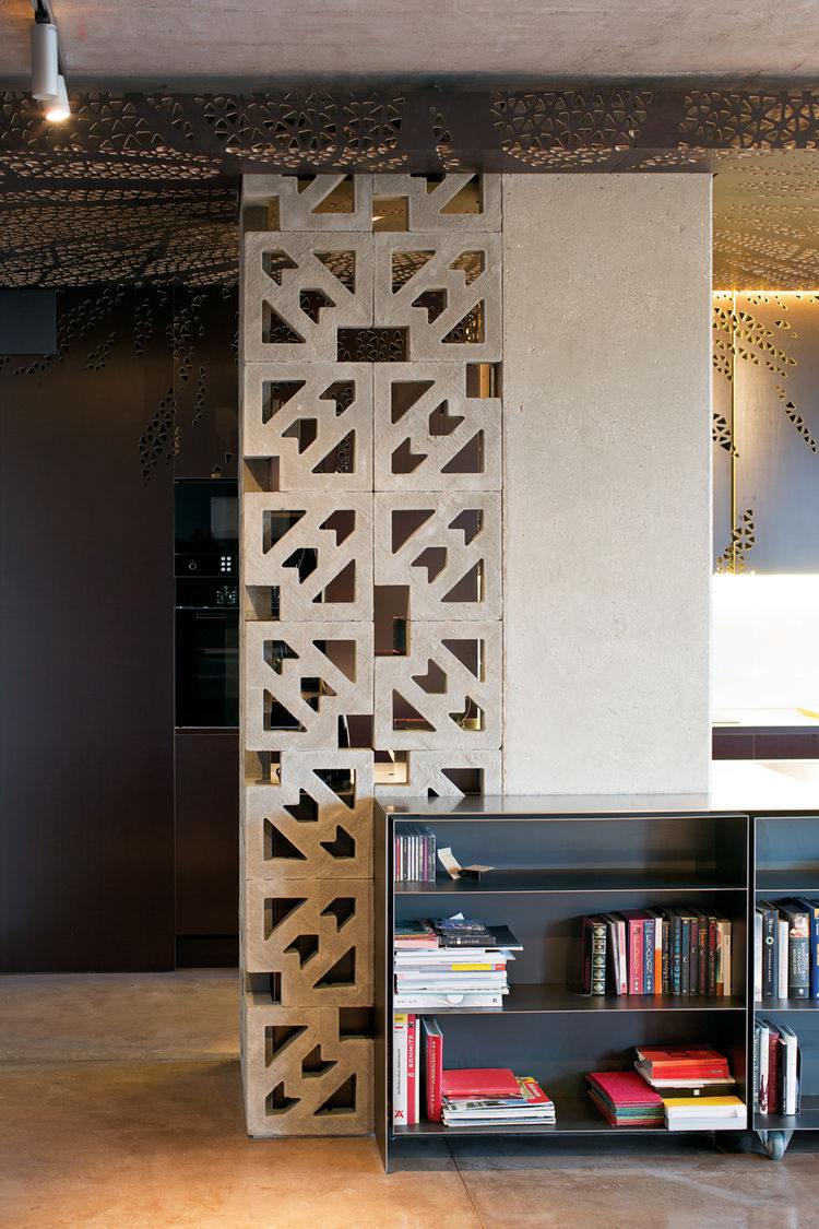 Modern custom-designed black-steel bookshelves and concrete wall