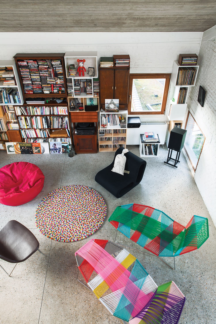 Modern living room with shelves and multicolored chairs.
