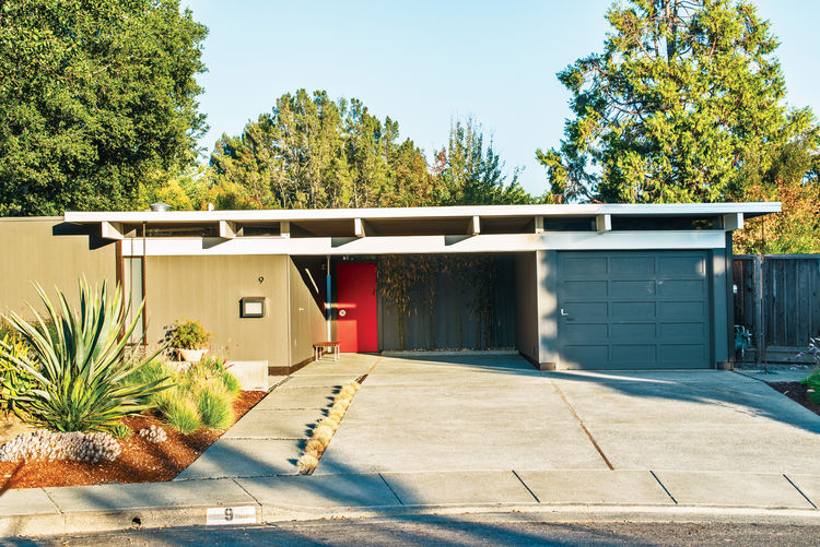 The exterior of Neely and Kefalides's house is punctuated with a bright red door.