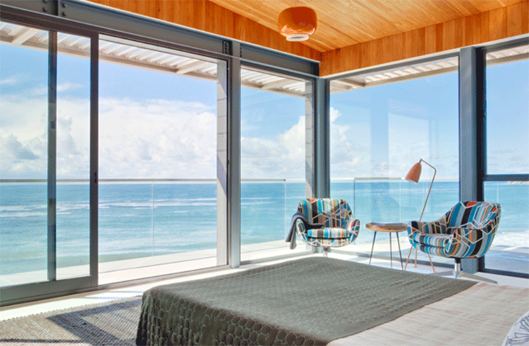 Oceanside bedroom with floor-to-ceiling glass windows