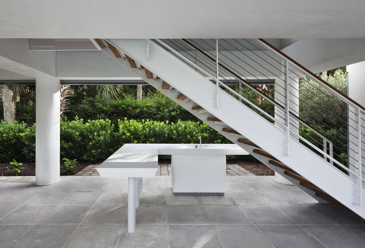 Minimalist outdoor kitchen under the pavilion is all-white with a cypress wood ceiling.
