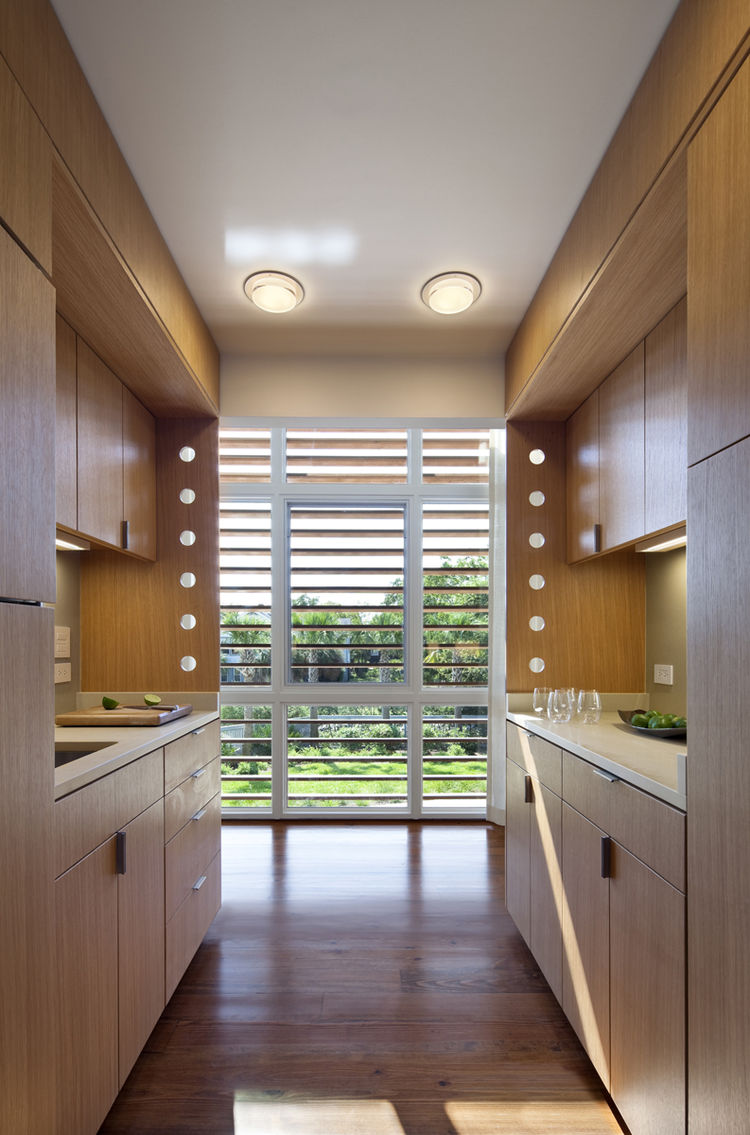 Sleek galley kitchen framed in wood works as a small space.
