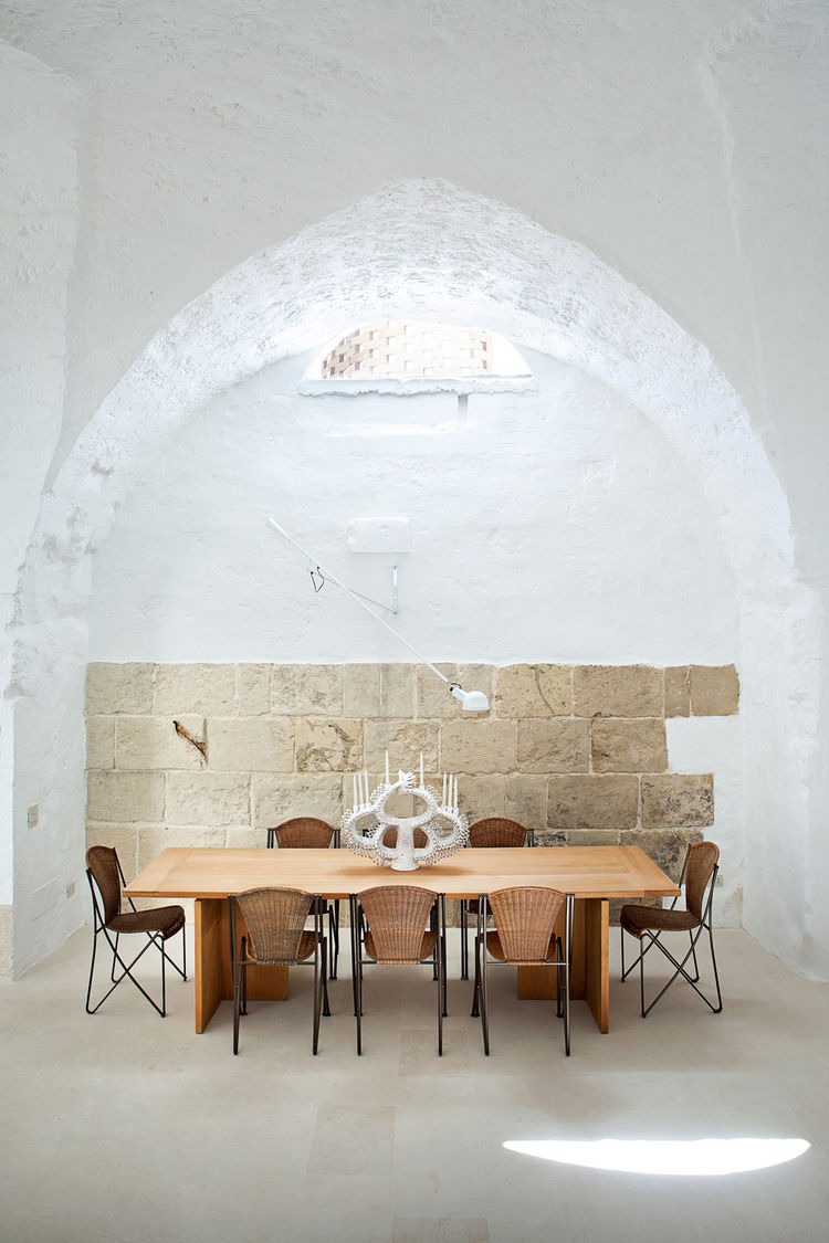 White dining room w/ wooden and wicker furniture.
