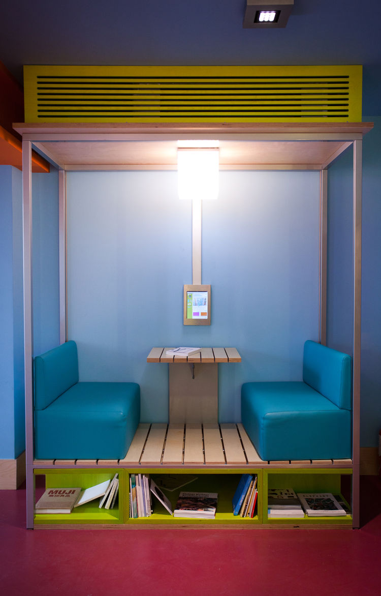 "Another cozy seating ""pod"" in the lobby, complete with reading material stowed in the cubbies below. It, like all of the furnishings, was designed by Crasset. ""The project is a renovation so the main challenge was not to break any walls or change the stru"