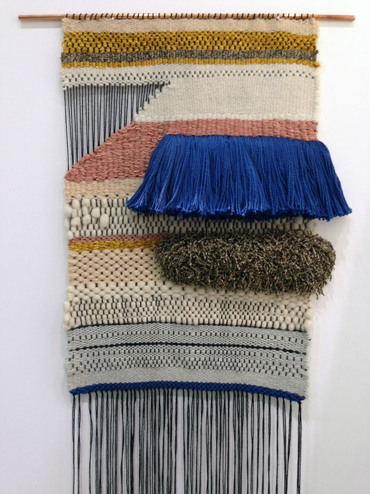 Woven textile wall hanging by Brook&Lyn in pink, gold, gray, and white yarn