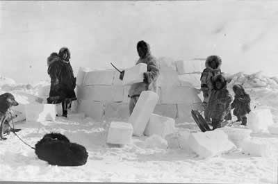 Inuit people building traditional igloo