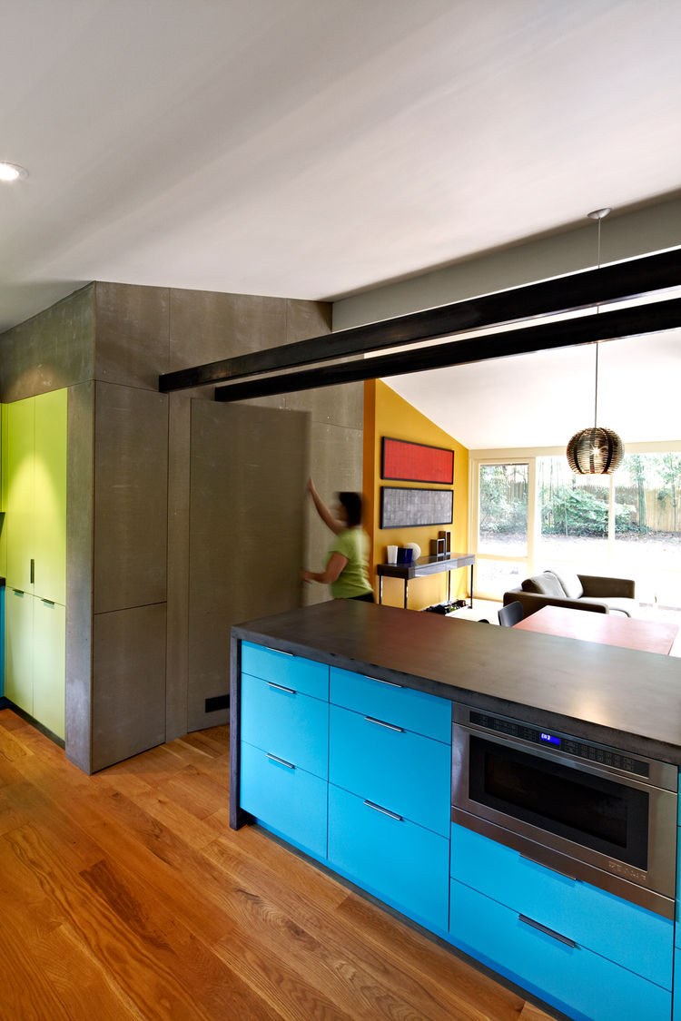 Modern kitchen renovation with dark concrete counter and blue cabinets