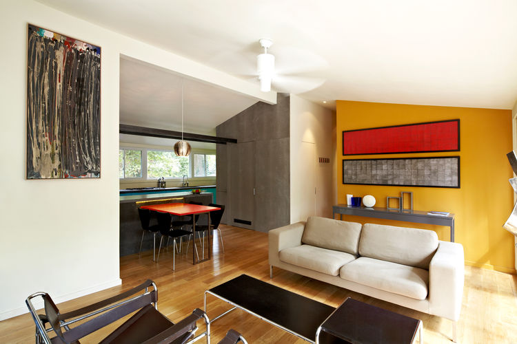 Modern dining room with gray sofa and wooden floors