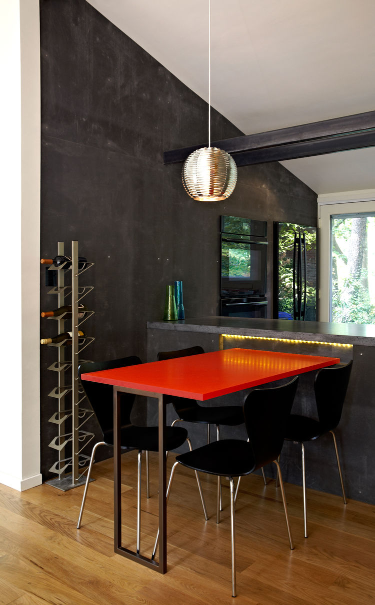 Modern dining area with red table and pendant ball light